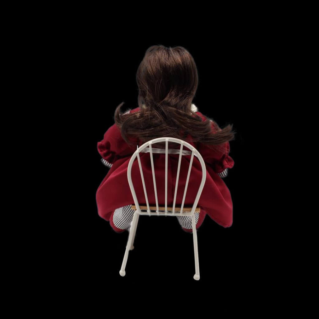 Lily sits in a chair, facing away