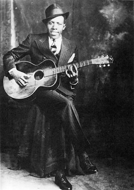 Black and white photo of Robert Johnson with a guitar