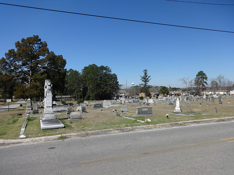 photo shows the cemetery from the road, with blue skies.