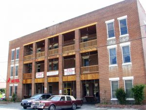 Photo shows the façade of the Walking Horse Hotel, with 10 balconies. The building is made of brick, with a couple of cars parked out front.