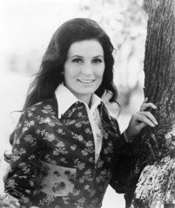 Photo shows Loretta Lynn, which long black hair leaning against a tree, smiling.