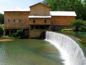 Photo shows the mill at Hurricane Mills. It is a large wooden building with a dam out front, water flowing over it.