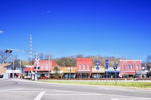 Photo shows part of downtown Wartrace, with small brick buildings and a railroad running in front of them. A blue sky sits behind.